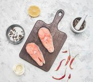 Two delicious raw salmon steaks with lemon, seasoning pepper on a white background, top view royalty free stock photo