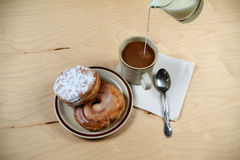 Two delicious sugared ring donuts served on white plate with a cup of hot drink Stock Images