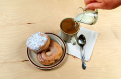 Two delicious sugared ring donuts served on white plate with a cup of hot drink Royalty Free Stock Photos