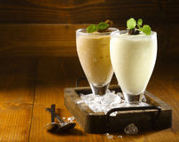Two delicious thick icecream milkshakes. Garnished with chocolate and mint and served in tall chilled glasses on a small old wooden tray royalty free stock photos