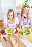Two delighted friends eating salad in the kitchen Royalty Free Stock Photography