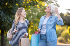 Two delighted pretty woman walking and having conversation. Royalty Free Stock Photos