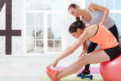 Two delighted women doing stretching in pairs Royalty Free Stock Photos