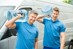 Two Delivery Men Delivering Bottles Of Water Royalty Free Stock Photography