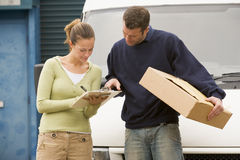 Two delivery people standing infront of van. Holding clipboard and parcel Royalty Free Stock Images