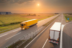 Two delivery trucks on the empty highway at sunset. New trucks driving towards the sun. Fast blurred motion photo on the freeway at beautiful sunset. Freight Royalty Free Stock Images