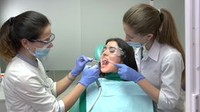 Two dental doctors and patient. Procedure at the dentist office stock video footage