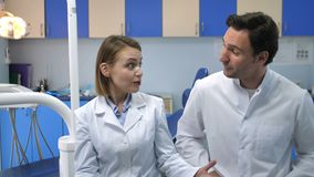 Dental doctors talking then smiling at camera. Two dental doctors in white lab coats sitting at modern dental office and talking, then looking at camera and stock video footage