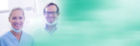 Two dentists smiling and blurry teal transition Royalty Free Stock Photos