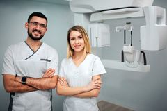 Two dentists stand in x-ray room and pose to camera. They smile and hold hands cossed. Professionals on picture. stock photos