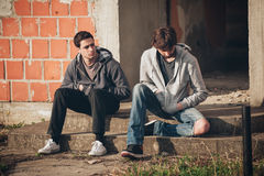 Two depressed and sad young buddies friends thinking about probl. Two depressed and sad young buddies friends thinking together about their problems Stock Image