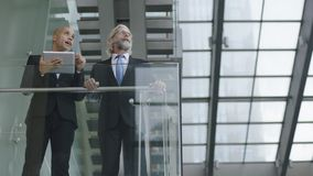 Design professionals having a discussion in modern building. Two design professionals standing in modern glass and steel building having a discussion using Stock Photo