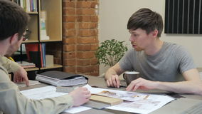 Two designers developing interior design sitting in office of company. They enthusiastically discuss technical project design stock video