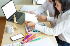 Two designers teamwork working with color samples for design project stock photo