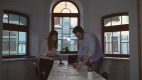 Two designers work with blueprint. Architect with assistant working in office. Adult man looking on architectural plan young woman writing notes in notebook stock video