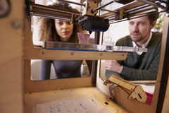 Two Designers Working With 3D Printer In Design Studio Stock Photos