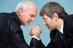 Two determined businessmen going head to head. In a challenge for supremacy staring into each others eyes and arm wrestling royalty free stock photos