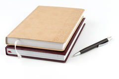 Two diary stacked lying next to a black pen. Stock Photography