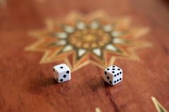 Two dice on the board to play backgammon in soft focus royalty free stock photo