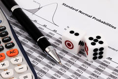 Two dice, calculator and pen on standard normal probabilities table. royalty free stock photos