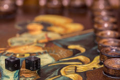 Two dice and chips on the backgammon table Stock Photo