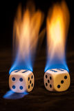 Two dice in flames on black tablecloth Royalty Free Stock Photos