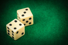 Two dice on a green gaming table Stock Image