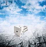 Two dice in motion, droughts desert , cloudy sky Stock Image