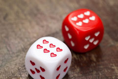 Two dices with hearts. On wooden table royalty free stock images