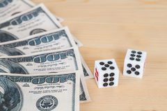 Two dices on wood table with  dollar Stock Photos