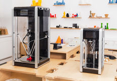 Two differen sizes of 3 D printers. Next to each other Stock Images