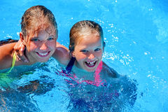 Two different ages children swim in swimming pool. Two different ages children hugging and looking up swim in swimming pool. Summer swimming holiday. Outdoor Royalty Free Stock Images