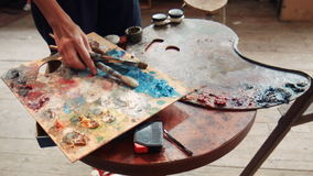 Two different artist pallets. Top down view on pair rectangular and spiral shaped artist pallets covered with globs of paint stock footage