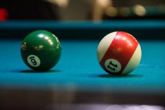 Two different balls for billiard. One of them green with number 6 and another white with red line and number 11 Stock Photos
