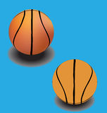 Two different basketball balls on blue. Backgroud Royalty Free Stock Images