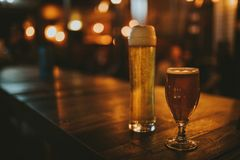 Two different beers on a wooden table. Two different beers on a wooden table, with pub lights in the background at night, and left copy space stock photos