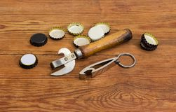 Two different bottle openers among of bottle caps on table. Vintage multipurpose bottle opener with wooden handle and bottle opener in the form of a keychain royalty free stock images