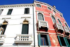 Two different buildings, one red seen from the Grand Canal in Venice in Italy. Photo made to the facades of two palaces in Venice in Italy. In the image, taken royalty free stock photography