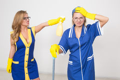 Two different cleaners compete. poor staff Royalty Free Stock Photography