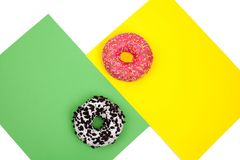 Two different donuts on green and yellow background stock photography
