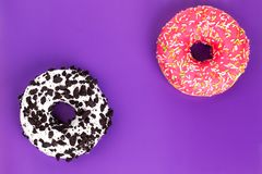 Two different donuts on purple background royalty free stock images