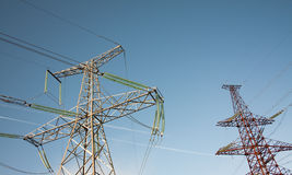 Two different electrical towers. Energy transmission from power plant to customers Stock Photo