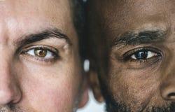 Two different ethnic men`s eyes closeup stock photos