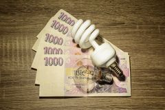 Two different European bulbs placed on Czech money stock image