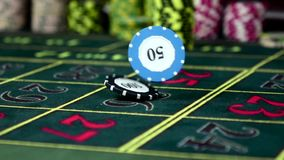 Two different gambling chip falling on roulette table, slow motion. Two different multicolored gambling chip falling down on a standart and usual roulette table stock footage
