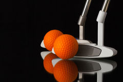 Two different golf putters on a black glass desk Stock Photos