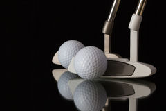 Two different golf putters on a black glass desk Royalty Free Stock Images