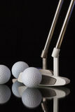 Two different golf putters and three golf balls Royalty Free Stock Photography