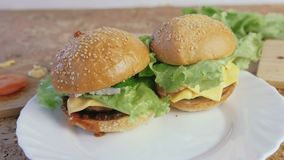 Two different homemade burgers on the white plate. Two different homemade burgers on the white plate stock footage