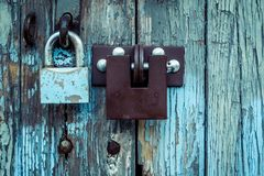 Two different locks on very old wooden garage door, peeling pain stock photography